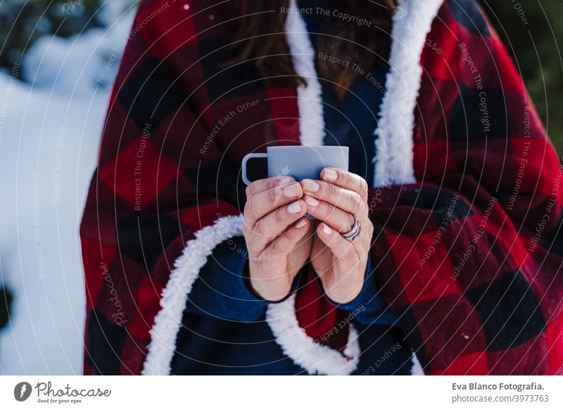beautiful woman wrapped in plaid blanket holding a cup of hot coffee. nature and lifestyle snow mountain hot tea thermos drink sunny hiking winter cold covered