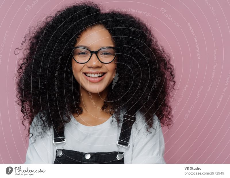 Close up portrait of dark skinned woman with crisp hair, smiles happily, wears optical glasses, casual clothes, poses over purple background expresses good emotions. Afro American student poses indoor