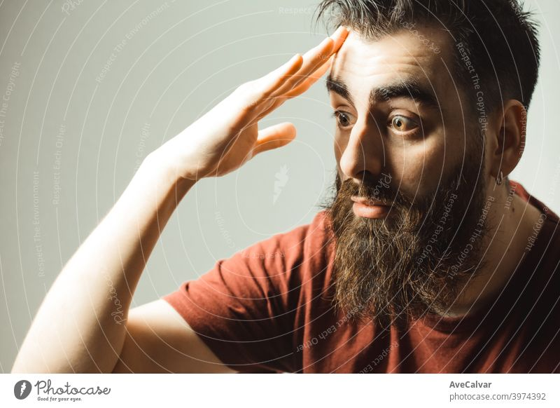 A young hipster style man with a beard and modern haircut surprised while looking at his phone with his phone screen with copy space win winner youth friendly
