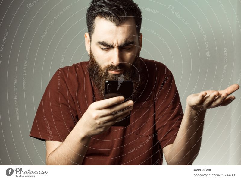 A young hipster style man with a beard and modern haircut angry while looking at his phone screen with copy space anxiety confused mistake anxious depressed