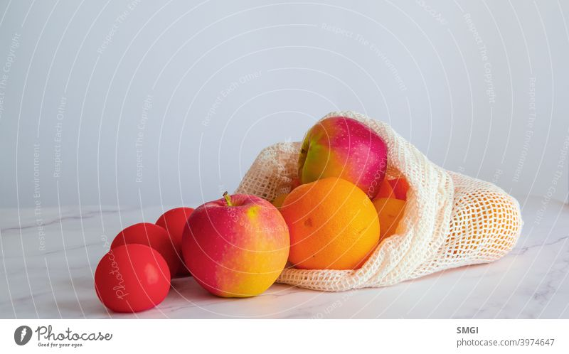 Different fruits and vegetables on a white table, inside a cloth bag. Concept of sustainable shopping and purchasing without plastics. Copy Space background eco