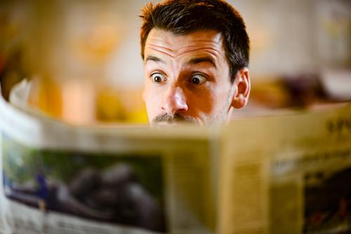 Man looks surprised in the newspaper Newspaper Reading astonished Media Press Current information world Facial expression Amazed shocked