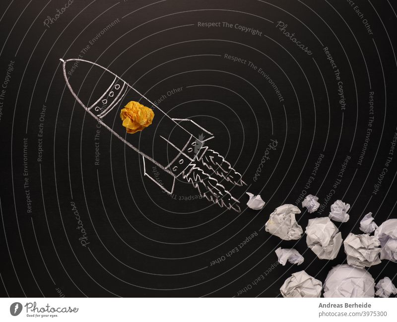 Launching rocket with jet stream of paper balls, creativity concept or new ideas metaphor, start up business light bulb black blackboard bright chalk chalkboard