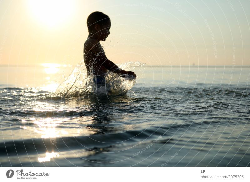 happy child in the ocean at sunset playing with water Faith & Religion background Forward Arm Hand Contentment Dance Posture Vacation & Travel Twilight