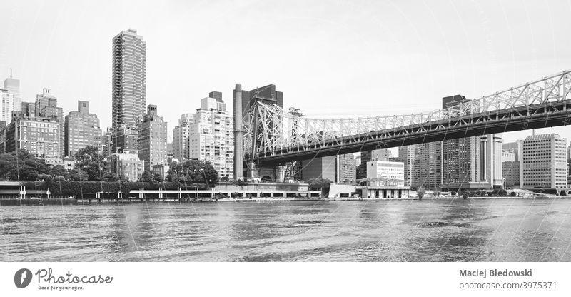 Panoramic view of Manhattan seen from Roosevelt Island, New York City, US. city cityscape skyline black and white building urban Queensboro Bridge bridge river