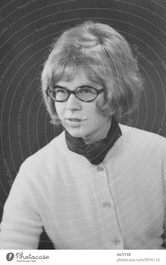 young woman in 60's with glasses wears hair style with man wink Nostalgia sixties portrait Eyeglasses Hairstyle Men's Wink smiling woman smilingly Cardigan