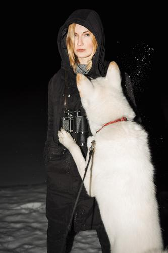 Blonde girl is playing with her white Akita-Inu dog. It's a cold winter night. A beautiful woman is feeling the freezing temperature as her cheeks are getting red. For some reason, she also has binoculars on her neck.