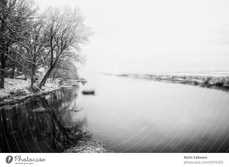 calm water in Latvian winter / river near my house / the day when ice forming on water / sunrise over land Autumn background cold color December February forest