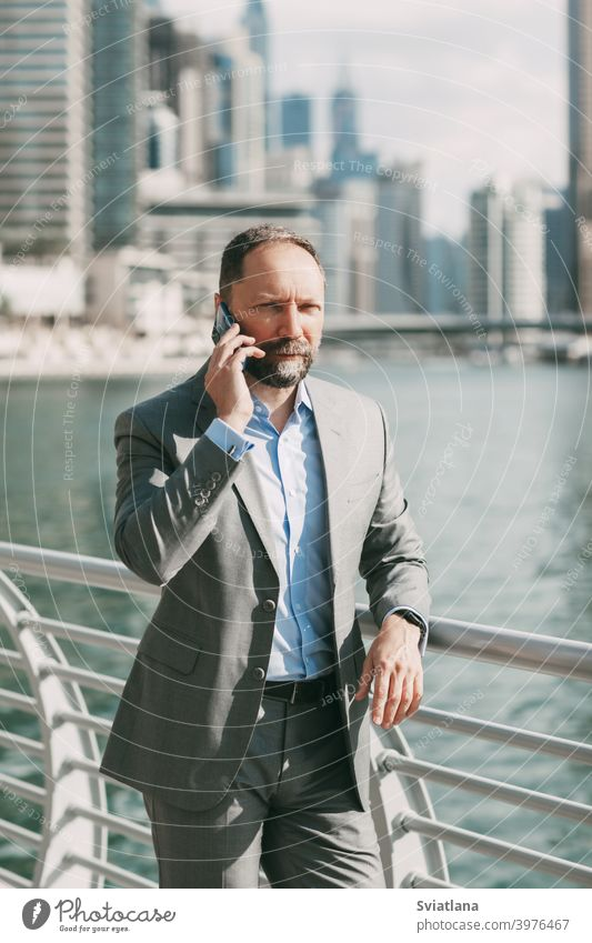 Young businessman with a phone in his hands, standing in a big city among high-rise buildings office smartphone modern successful suit happy employer flash