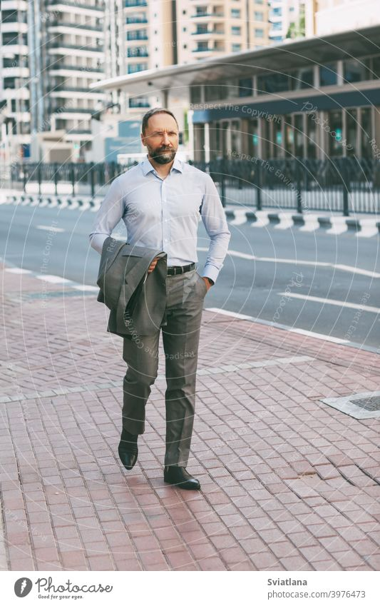 Portrait of a young millennial walking in the city with a phone in hand office man businessman smartphone modern successful suit happy employer flash light