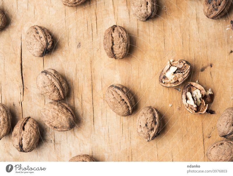 walnut in shell on a wooden table whole background broken brown closeup cracked food fresh fruit group hard healthy ingredient kernel natural nature nutrition
