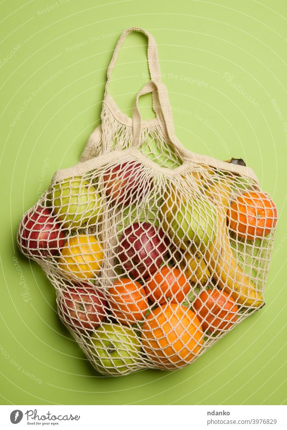 ripe fresh fruits in a textile string bag on a green background orange apple banana concept cotton eco ecological ecology food friendly grocery harvest health