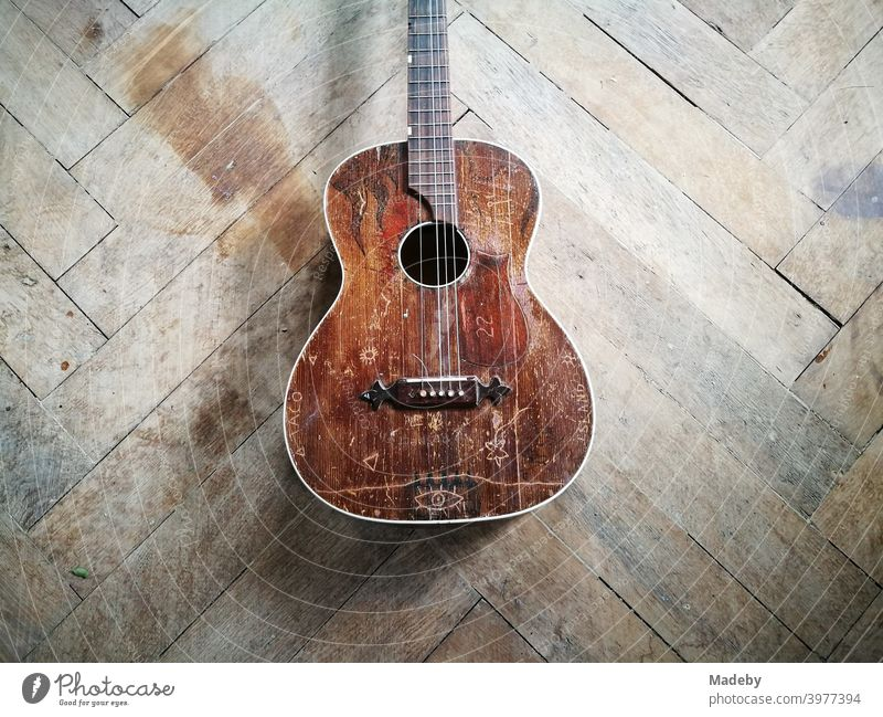 Old brown broken guitar with broken string on the beautiful old wooden floor of a farmhouse in upper bavaria Guitar Musical instrument string Hippie Broken