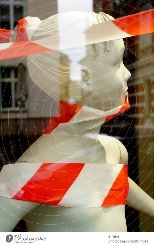 In the shop window is a white, childlike mannequin with red and white barrier tape wrapped around it / business liquidation / clearance sale / sale Mannequin