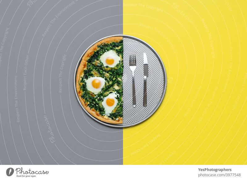 Vegetarian pizza with egg and spinach, top view. Half pizza isolated on grey and yellow color Italian cheese color of the year colored background