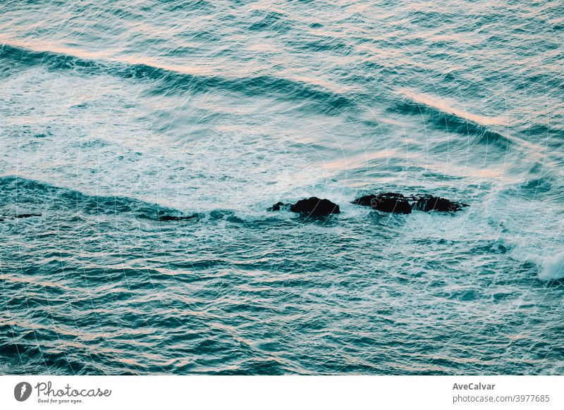 Aerial view of the ocean with the waves and re rocks during a bright day, relaxing scene on blue tones oceans copy-space meditation calmness textures peace awe