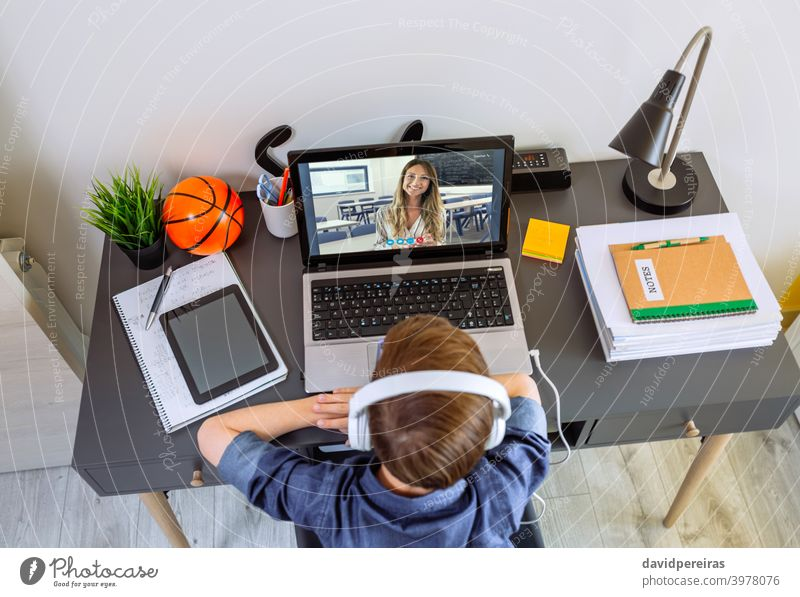 Top view of unrecognizable boy with headphones receiving class at home with laptop top view teenager teacher school at home video call desk home schooling