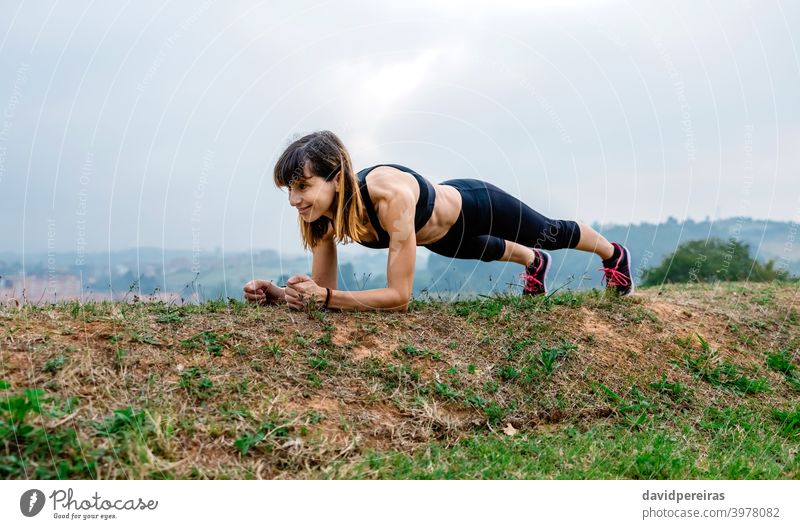 Female athlete training doing plank woman smiling morning abs enjoying endurance effort outdoors sportswoman fitness female athletic healthy workout young