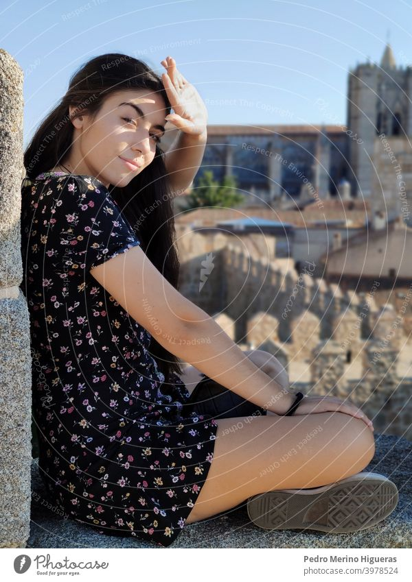 Beauty woman covering the sun with her hand, sitting on a wall women beauty white girl caucasian brown hair model dress cathedral avila spain sunny clear sky
