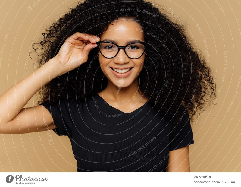 Lovely young African American woman grins at camera, keeps hand on rim of spectacles, glad to hear good news, dressed in casual black t shirt, isolated over brown background. Happiness concept