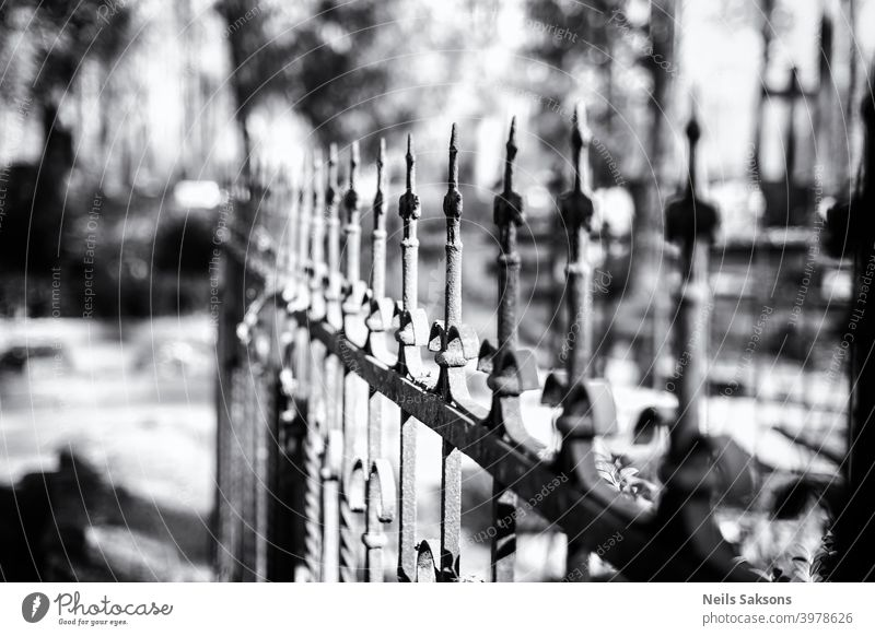 Hundred years old cast iron fence around family grave in some country cemetery in Latvia. Perspective made of many equal art masterpieces. ancient antique