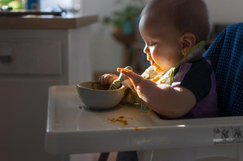 Baby seated in high chair reaching for spoon; dramatic natural lighting and messy tray table baby led weaning first foods finger foods dramatic lighting