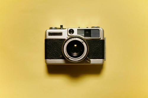 front view of vintage analogue photo camera isolated on yellow background old equipment film lens antique classic photography retro black metal technology white