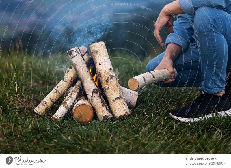 traveler man on camping in the mountains outdoor. setting up camping fire. forest winter match young flame firewood nature bonfire tourism campfire male pile