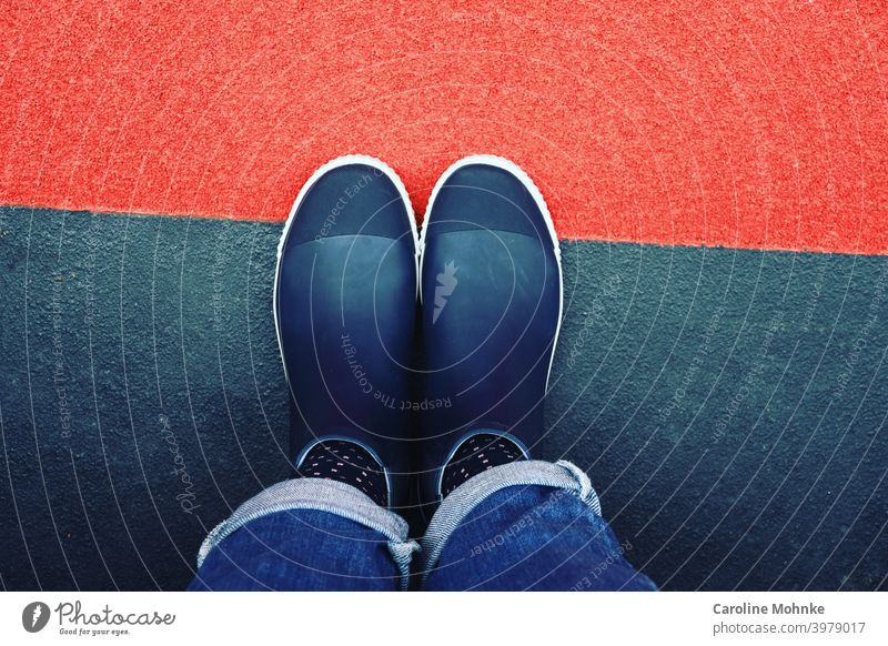 Woman standing in blue half rubber boots and jeans on red blue floor Footwear Rainboots Rubber boots Boots Exterior shot Wet Water Colour photo Weather