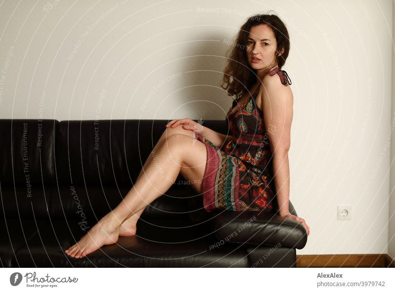 Portrait of a young brunette long haired woman sitting barefoot on a dark couch in a summer dress Woman naturally pretty Brunette Long-haired long hairs Slim