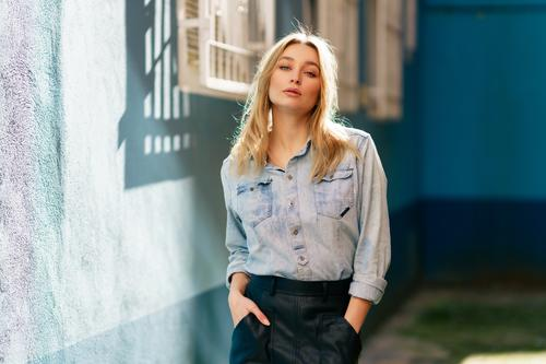 Blonde woman wearing denim shirt and black leather skirt standing in the street. girl female blonde russian blue eyes portrait fashion outdoors lady hairstyle