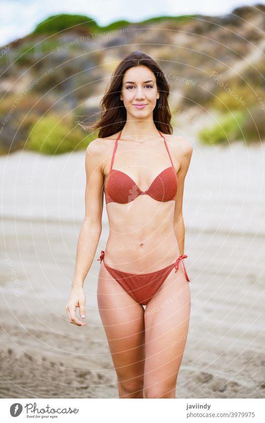 Portrait of a woman with beautiful body on a tropical beach bikini swimsuit summer leisure lifestyle female girl coast hair one cute hairstyle season sand model
