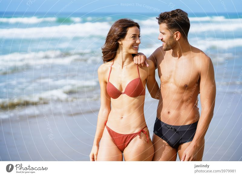 Young couple of beautiful athletic bodies walking together on the beach woman bikini summer body leisure lifestyle female girl coast outdoors enjoying people