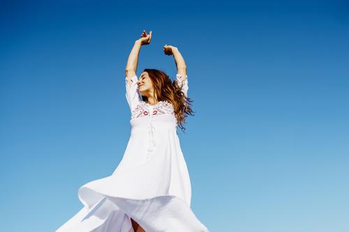 Young woman raising her arms in a beautiful white dress against a blue sky fashion girl wave open hair female copyspace extensions hairstyle fashionable model