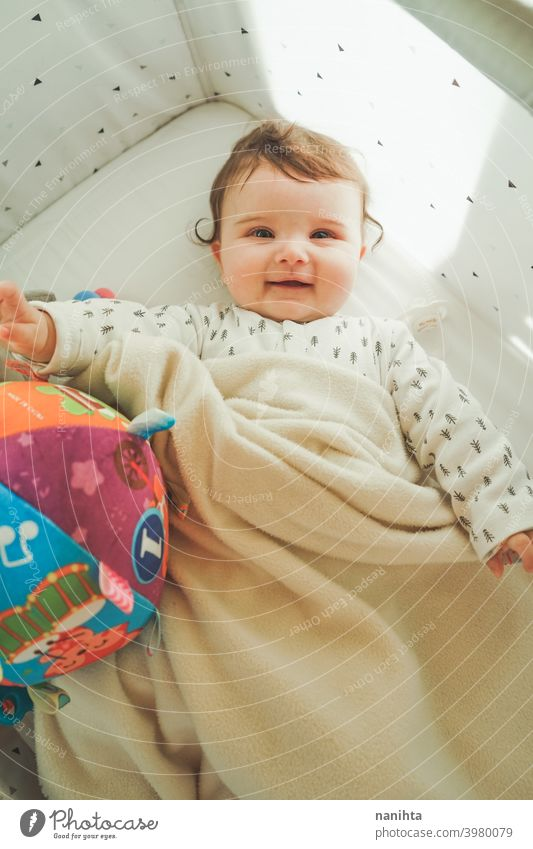 Portrait of a little playful baby in her cradle childhood family love happy cute hapiness warm soft kawaii adorable baby girl kid parenthood crib toys infancy