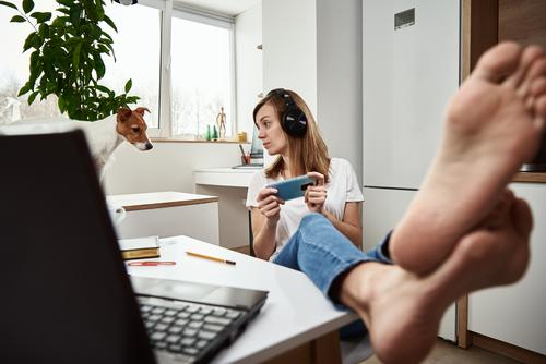 Woman listening online course in headphones, distance education. Freelancer sitting at workplace and procrastinating. Lazy and distracted employee at remote work