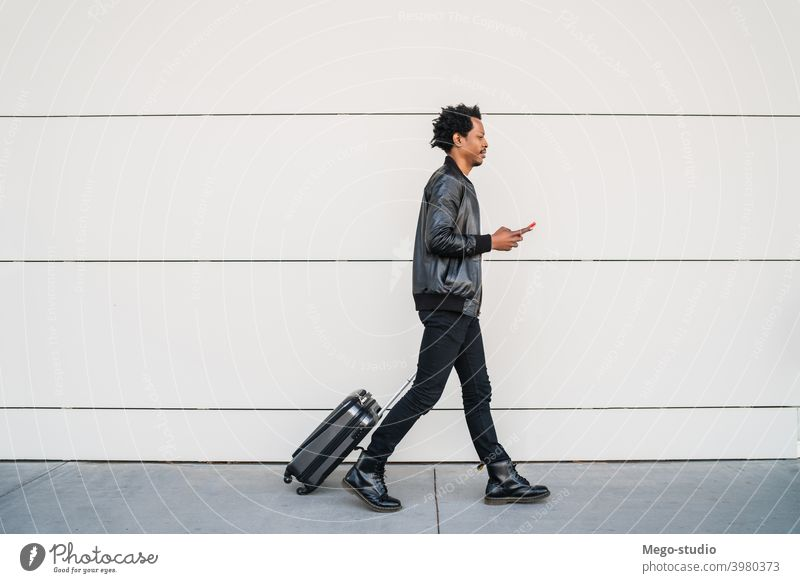 Tourist man using his mobile phone and carrying suitcase outdoors. tourist communication business text black cell sms holiday city journey enjoy telephone afro