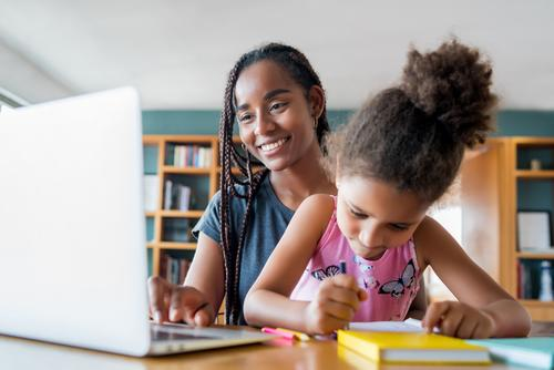 A mother helping her daughter with homeschool. laptop online homework student learning lifestyle quarantine family children people lock down indoor motherhood