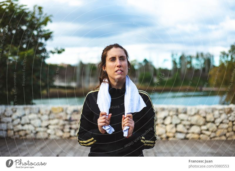 Tired sporty woman with towel relaxing after hard workout at park. fit girl health lifestyle training video wellness aerobics alone balance body class coach