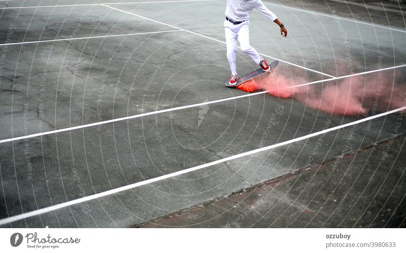 Skateboarder playing at tennis court with pink smoke on skateboard skateboarding Pink Smoke urban sport skater young lifestyle Tennis court skateboarder youth