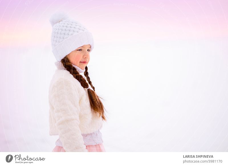 Portrait of little girl on walk in winter in early frosty morning. cold face hat beautiful young snow christmas portrait cute happy fashion white outdoor people