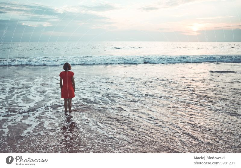 Woman stands in the ocean at sunset. girl beach water woman sea loneliness depression summer nostalgia faded sky horizon wave female sunrise young vacation
