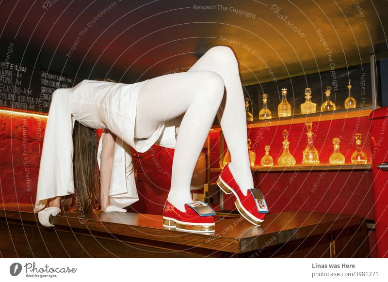 Once upon a time when you could dance on a bar. With your red and shiny shoes, white outfit, and red light all over the place. Pretty and long legs are dominating the place as well.
