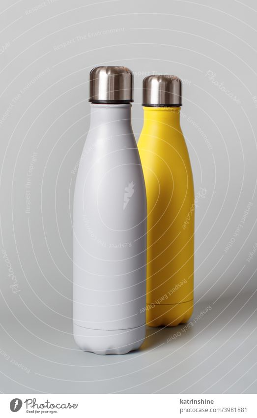 Grey and yellow reusable bottles on grey background monochrome mockup insulated ecologic water steel thermo aluminum blank close up concept copy space