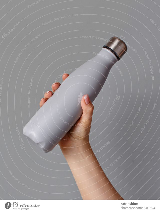 Hand with grey rinsulated bottle on grey background reusable hand monochrome mockup yellow ecologic water steel thermo aluminum blank close up concept