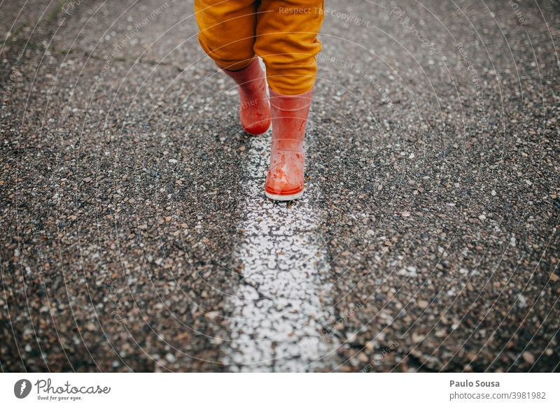Close up child red rubber boots walking the line Red Rubber boots Line Walking Child Wet Infancy Water Human being Joy Exterior shot Rain Playing Colour photo