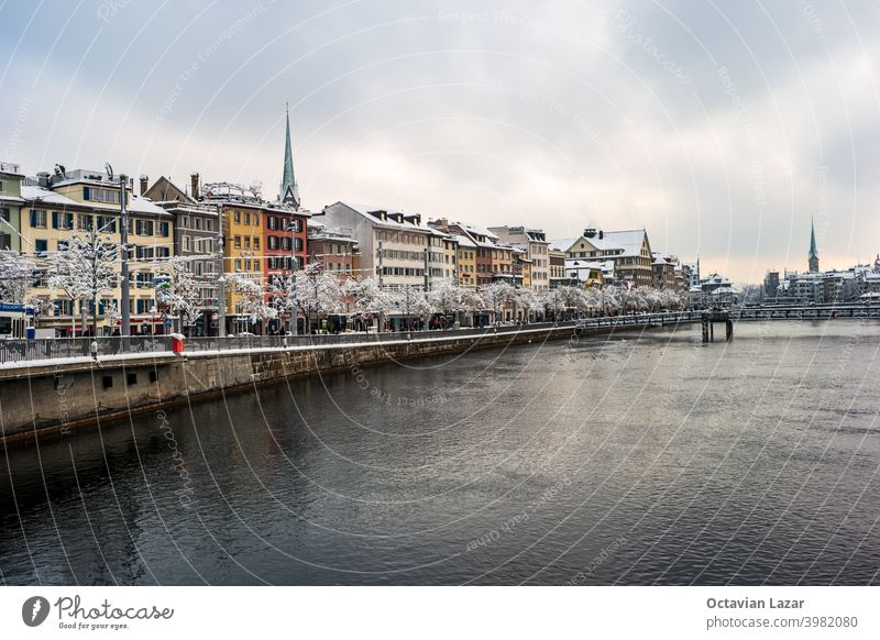 Waterside view of snow covered Zurich city Switzerland from a bridge crossing the Limmat river winter time cloudy day record snowfall white outdoor old town
