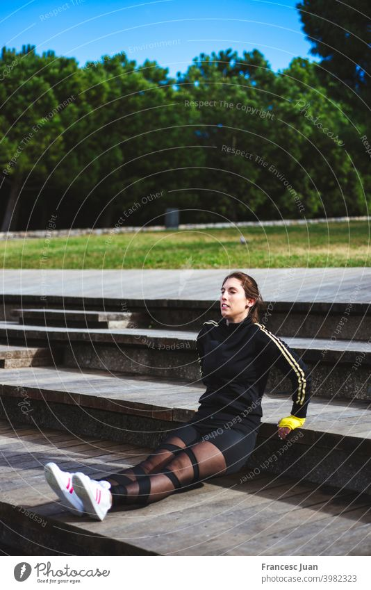 Beautiful adult woman is exercising outdoor at park. Reverse push-ups. 30s active arm athlete autumn beautiful body brown hair city cloudy cold copy space day