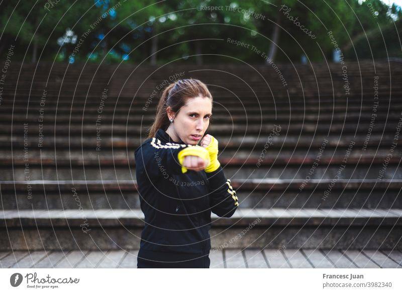 Girl training body combat at park. Self defense concept action athlete bandage battle boxer boxing brunette caucasian competition copy space energy female