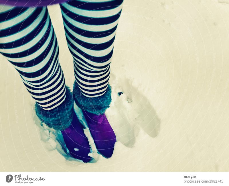 A woman is standing in the snow.  Next to her two empty footprints. She wears black and white striped stockings and purple boots. Footwear Boots Snow Feet Legs